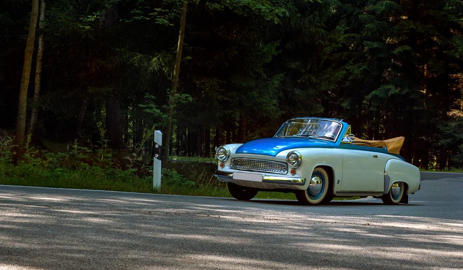 Wartburg Cabrio blau weiß auf kurviger Landstraße im Wald